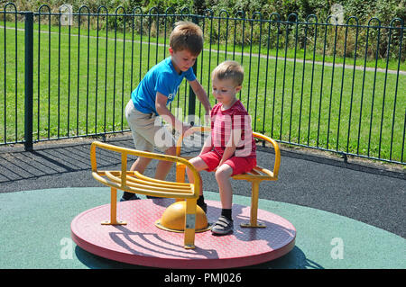 Two small boys playing on a roundabout in a play park. - Stock Photo