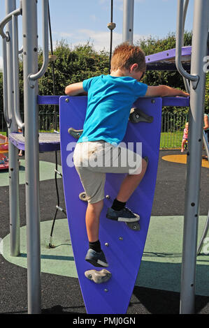 Seven-year-old boy climbing a climbing wall up to a slide in a play park. - Stock Photo