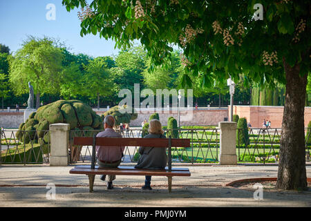 Mature couple sitting on the bench in the park (Parque del buen retiro in Madrid, Spain) - Stock Photo