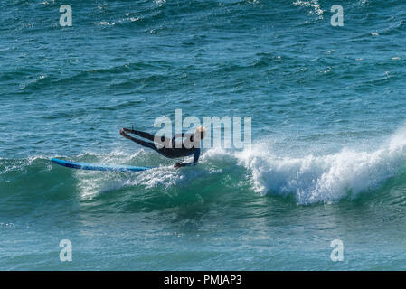 A surfer falling off his surfboard at Fistral in Newquay in Cornwall. - Stock Photo