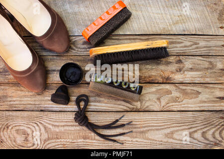 Shoes and care products for footwear on wooden background. Toned image. Top view. - Stock Photo