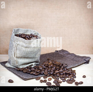 Coffee beans in burlap sack and coffee beans spread across surface. - Stock Photo