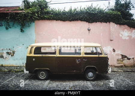 Brown and cream retro campervan from the 1970s parked along a cobbled street with pastel pink and blue walls - Stock Photo