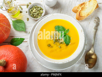 Dietary vegetarian pumpkin cream soup puree with olive oil, seeds and Basil on a light wooden table in a white plate. Selective focus - Stock Photo