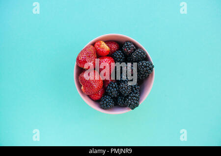 Flat lay of freshly picked various berries in a bowl on blue background. - Stock Photo