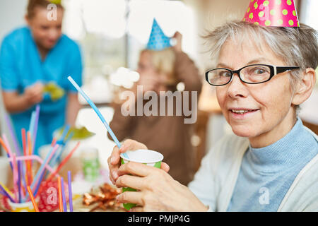 Senior woman in retirement home celebrates birthday together with friends and family - Stock Photo