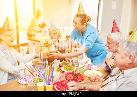 Seniors celebrate birthday together in the retirement home with cake and gift - Stock Photo