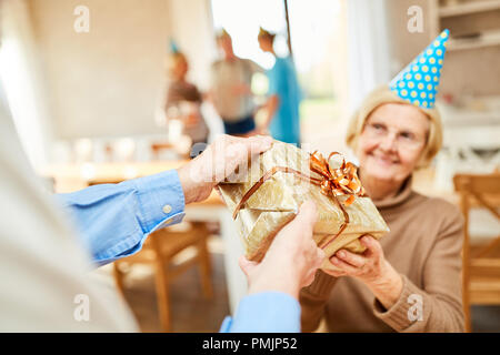Senior woman is surprised with a gift at her birthday party in retirement home - Stock Photo