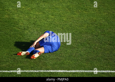 An injured football player laying down on the grass floor in pain and holds his leg. - Stock Photo