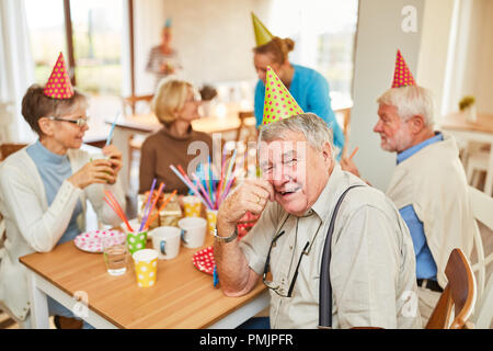 Seniors celebrate birthday together in a retirement home and have fun together - Stock Photo