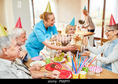 Nursing help gives a birthday present to a senior citizen at the coffee table in the retirement home - Stock Photo