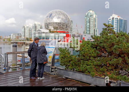 Middle aged tourist couple looking at a map on the dock at the Village on False Creek, Vancouver, BC, Canada - Stock Photo