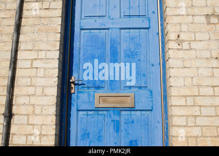 Brass door letterbox on a blue vintage front door on a  yellow brick wall - Stock Photo