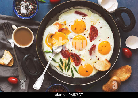 Flat lay fried eggs with tomatoes in a pan, toast with butter, coffee. A hearty Breakfast on a blue background - Stock Photo