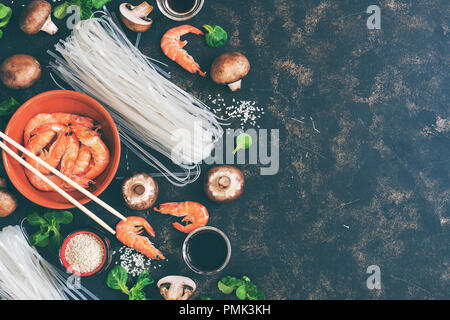 Background with Asian ingredients - rice noodles, shrimps, mushrooms, sesame, salad corn, dark background. Flat lay,copy space. toned photo - Stock Photo