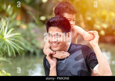Asian father play with son good relationship happy smile in the park family man concept. - Stock Photo