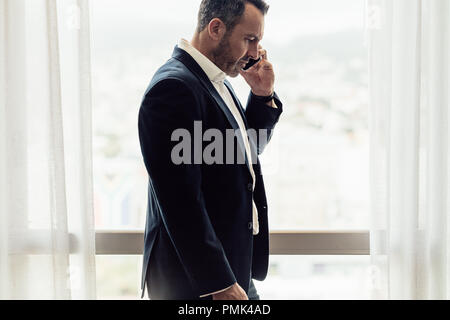 Side view of mature businessman talking on cell phone. Man in hotel room having discussing over phone. - Stock Photo