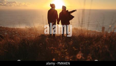 Rear view silhouette of couple standing on the mountain peak, with woman showing something to man. Traveling couple overlooking the seascape during su - Stock Photo