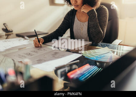 Female architect working on house floor designs at her work desk. Woman preparing new building plan while sitting at her work desk. - Stock Photo