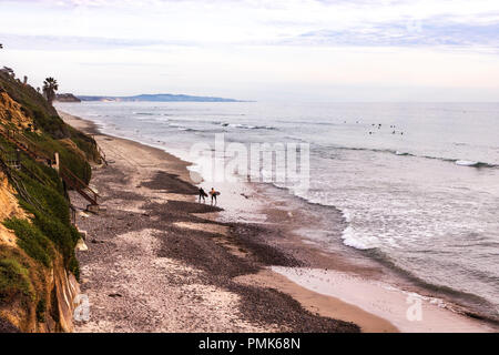 Two surfers walk up a rocky shoreline beach with surf rolling in, green hillside and peninsula in sunset background - Stock Photo