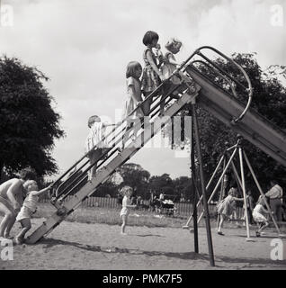 1950s, historical, young chiidren outside in a playground up high on the steps of a traditional metal slide, England, UK. - Stock Photo