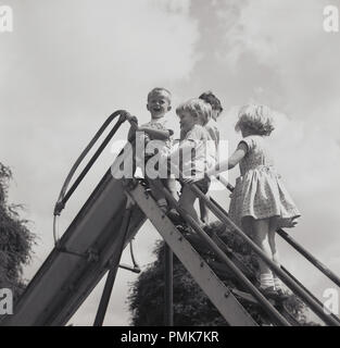 1950s, historical, young chiidren standing at the top steps of a metal playground slide, England, UK. - Stock Photo