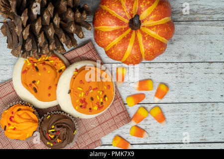 Orange iced sugar cookies and fall Halloween themed cupcakes - scattered candy corn. Pine cones and pumpkins, wooden background. Concept for fall - Stock Photo