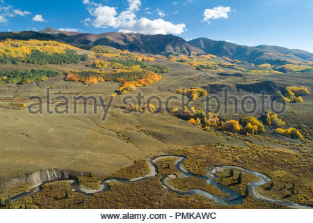 The East River snakes across the valley floor below Whiterock Mountain in western Colorado decorated with fall colors. - Stock Photo