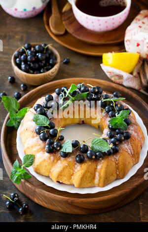 Delicious dessert black currant, sweet delicious holiday cake with black currant and lemon glaze on a table in a rustic style. - Stock Photo