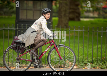 London cycling in Hyde Park UK. Individual female cyclist, on the traffic free cycling path enjoying her way back home, coming from work. - Stock Photo