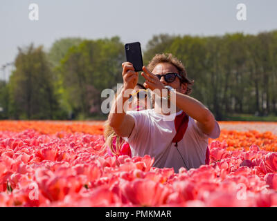 Lisse, APR 21: Couple taking selfies in a blossom Tulips farm on APR 21, 2018 at Keukenhof, Lisse, Netherlands - Stock Photo