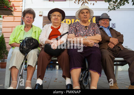 A group of friends sitting on a bench in Sibiu, Romania - Stock Photo
