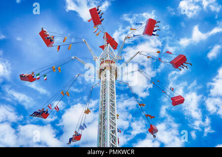 people on a ride going up to the top of the ride on a sunny day with clouds in the sky. - Stock Photo