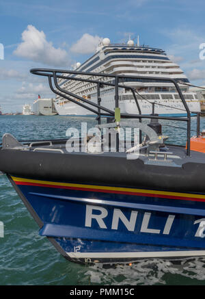 an RNLI lifeboat with the navigator  of the seas massive cruise liner in the background. - Stock Photo