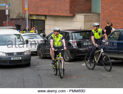 Gardaí officers on bicycle patrol wearing helmets and high visibility reflective vest, Fishamble Street, Christchurch, Dublin, Leinster, Ireland - Stock Photo