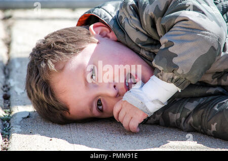 Toddler throwing a tantrum on the ground - Stock Photo