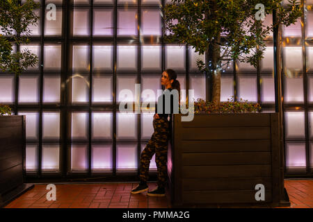AUCKLAND, NEW ZEALAND - SEPTEMBER 14 2018; Girl leaning looking pensive on planter in front of panneled back-lit wall in Auckland's Britomart area - Stock Photo