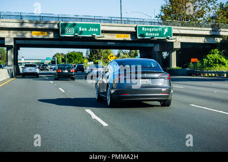 April 21, 2018 Mountain View / CA / USA - The new Model 3 Tesla driving on the freeway in Silicon Valley, south San Francisco bay area - Stock Photo