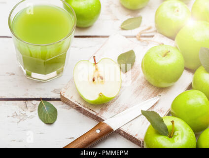 Glass of fresh organic apple juice with granny smith and british bramley apples on wooden background. - Stock Photo