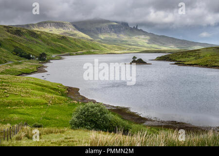 Dappled sun on The Storr mountain peaks with The Old Man of Storr in clouds over Loch Fada Isle of Skye Scottish Highlands Inner Hebrides Scotland - Stock Photo