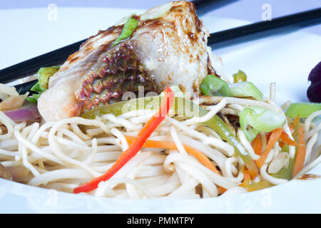 Middle eastern style dish of pan fried Red Snapper with stir fried vegetables and Chinese egg noodles topped with a Teriyaki sauce. - Stock Photo