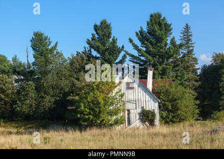 Old deserted and ramshackle farmhouse with leaning chimney. Knowlton, Quebec, Canada - Stock Photo