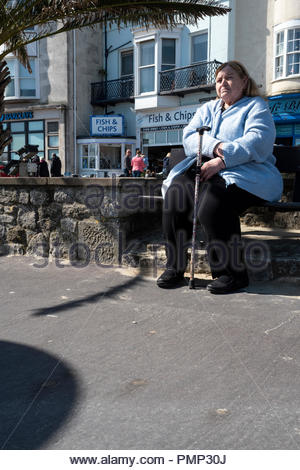 A woman with a walking stick sits on her own in the sunshine at Weymouth, Dorset, England, UK - Stock Photo