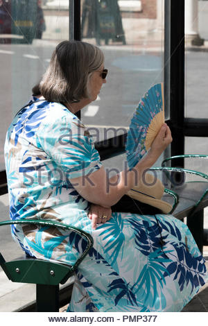 Older woman sits fanning herself whilst waiting for a bus during the 2018 heatwave, Blandford Forum, Dorset, England, UK - Stock Photo