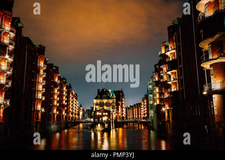 Hamburg, Germany. View of Wandrahmsfleet at dusk illumination light with clouds above. Located in Warehouse District - Speicherstadt Landmark of HafenCity quarter. Most visited touristic famous place - Stock Photo