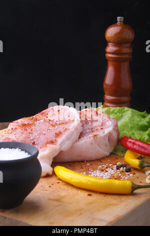 Raw steak, chop on a rustic cutting board with salt, pepper and grinder for spices . Black Background for copy space. Top View. - Stock Photo