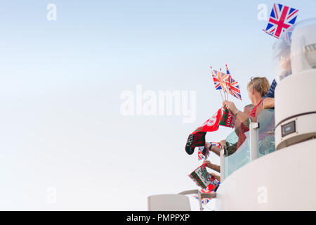 British people waving the Union Jack flag and a Welsh banner/ scarf on a cruise ship sail away - Stock Photo