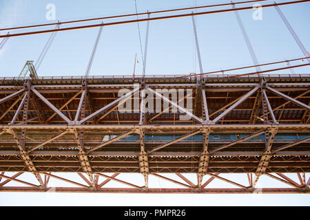 A close up of the 25 de Abril Bridge, a suspension bridge in Portugal connecting Lisbon and Almada - Stock Photo