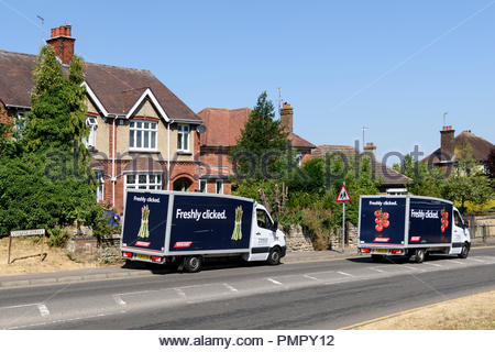 A Tesco delivery van drives by another Tesco van parked at the roadside, Higham Ferrers, Northamptonshire, England, UK - Stock Photo