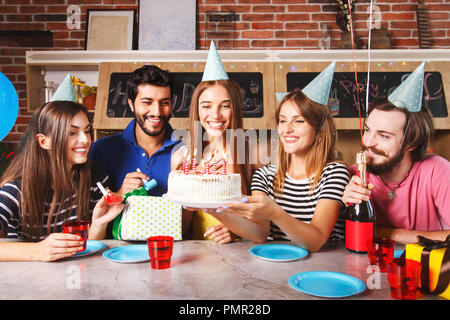 Excited woman ready to blow out candles on white frosting cake on table at birthday party with happy friends - Stock Photo